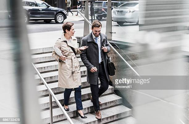 Businessman and woman walking down stairs