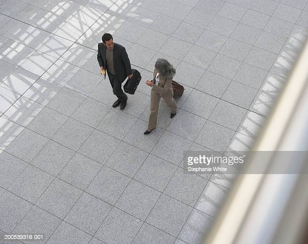 Businessman and woman walking in airport, overhead view