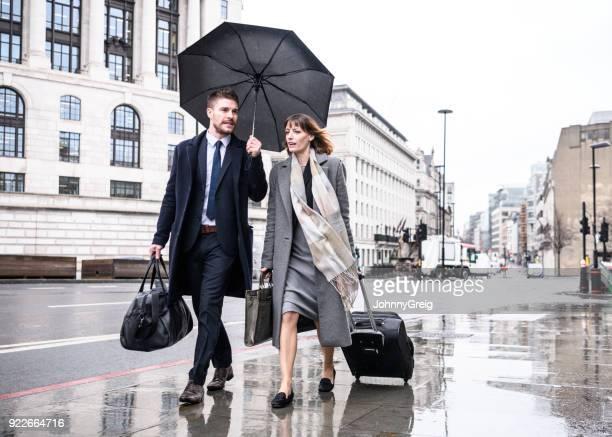 Geschäftsmann und Frau zu Fuß auf dem Bürgersteig mit Gepäck