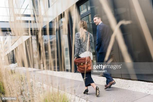 businessman and woman walking outside office building - gemeinsam gehen stock-fotos und bilder