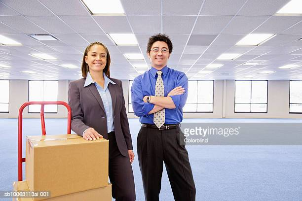 Businessman and woman with boxes on dolly in empty office, smiling, portrait