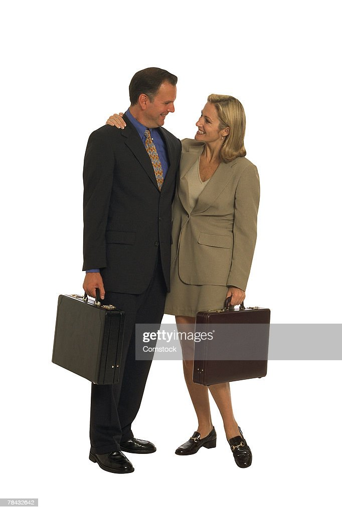 Businessman and woman with briefcases embracing : Stockfoto