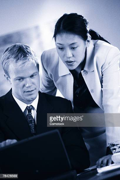 Businessman and woman working at laptop computer