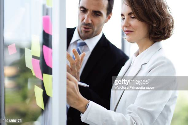businessman and woman working on computer together in office. - routine stock pictures, royalty-free photos & images