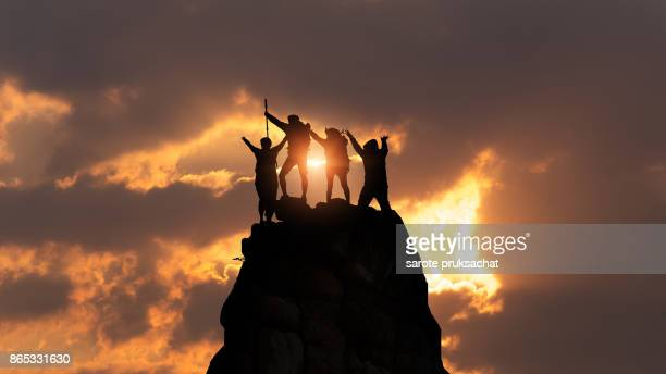 businessman and women group hike on the peak of silhouette rocks mountain at sunset, success, winner, leader concept - achievement stock pictures, royalty-free photos & images