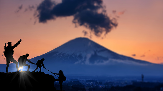 Businessman and women group hike on the peak of silhouette rocks mountain at sunset, success, winner, leader and teamwork concept . - gettyimageskorea