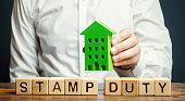 Businessman and wooden blocks with the word Stamp duty and house. Taxes assessed during the transfer of real estate between two parties. Buying housing and land. Property. Stamp Duty Land Tax/ SDLT