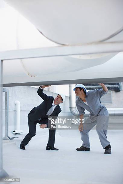 Businessman and worker checking on large pipe outdoors