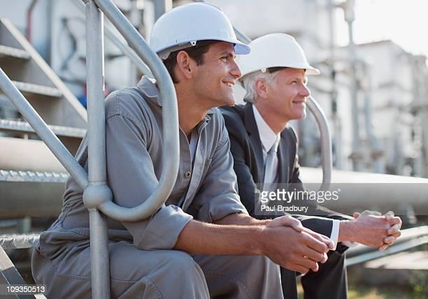 Geschäftsmann und Arbeiter in harten-Hüte sitzen auf den industrial Schritte