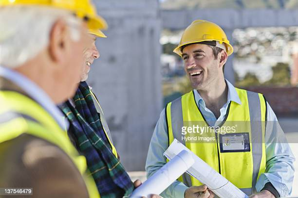 Businessman and workers talking on site