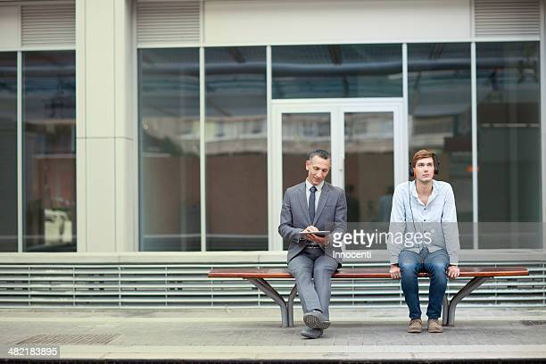 Businessman and young man sitting on train station bench