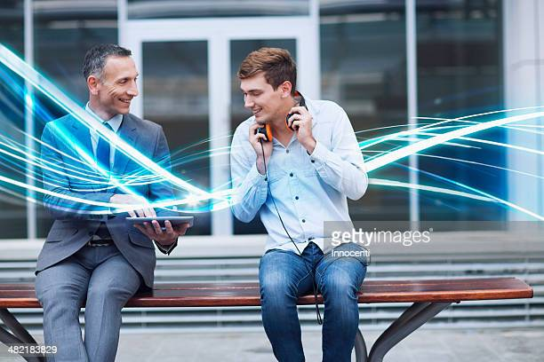 businessman and young man watching digital tablet and waves of blue light - data stream stock photos and pictures