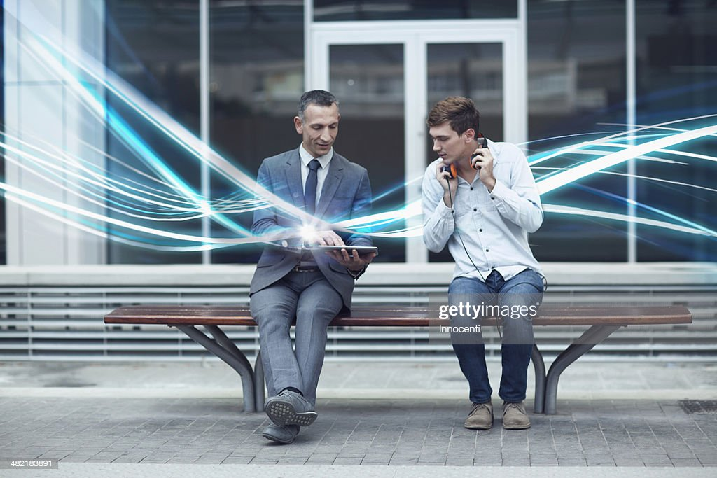 Businessman and young man watching digital tablet and waves of illumination : Stock Photo