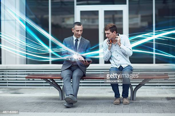businessman and young man watching digital tablet and waves of illumination - holy city stock pictures, royalty-free photos & images