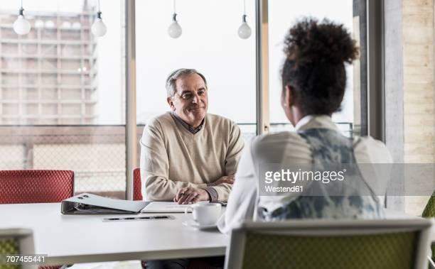 businessman and young woman in conference room - pareja hombre mayor y mujer joven fotografías e imágenes de stock