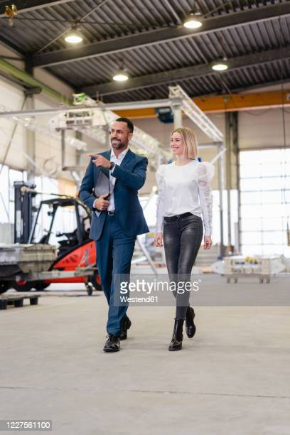 businessman and young woman walking and talking in a factory - gemeinsam gehen stock-fotos und bilder
