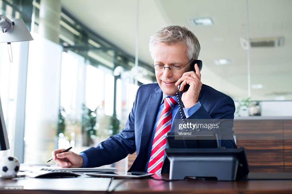 Businessman answering a phone call : Stock Photo
