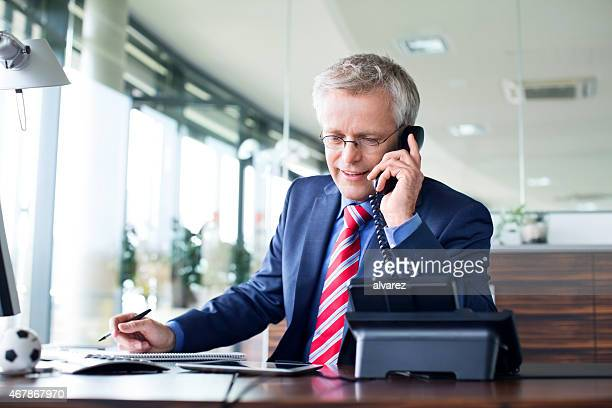 businessman answering a phone call - fastnät bildbanksfoton och bilder
