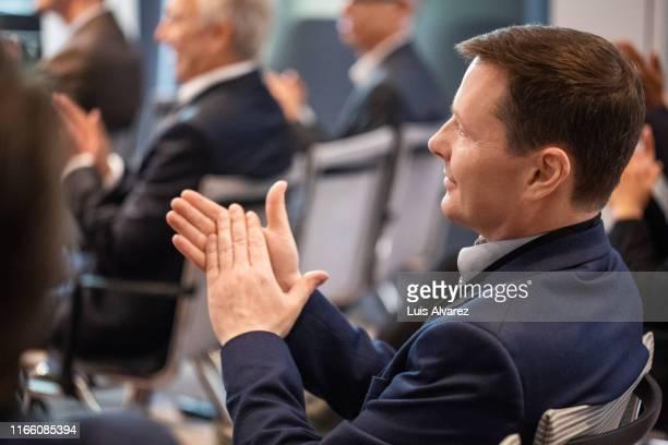 businessman applauding during seminar - pressekonferenz stock-fotos und bilder
