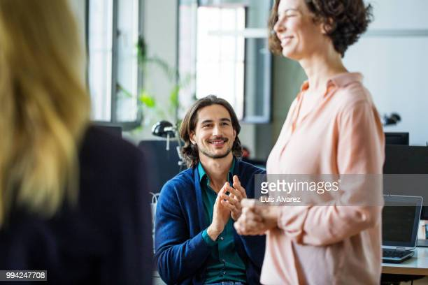 Businessman applauding while looking at colleague