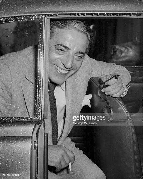 Businessman Aristotle Onassis smoking in the back of his car arriving in Monte Carlo for the wedding of Grace Kelly Monaco April 14th 1956