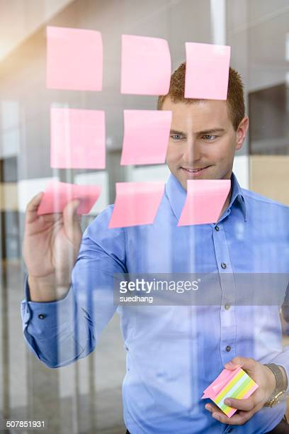 Businessman arranging post it notes on office window