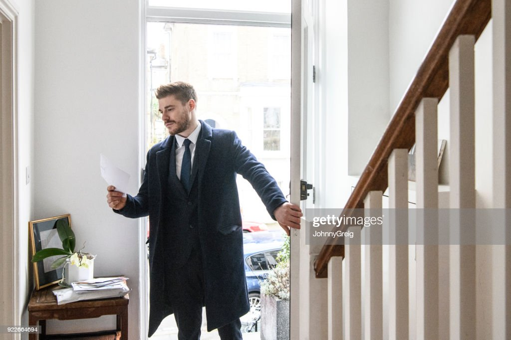 Businessman arriving home and checking post in hallway : Stock Photo