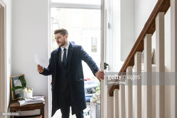 businessman arriving home and checking post in hallway - arrival stock pictures, royalty-free photos & images