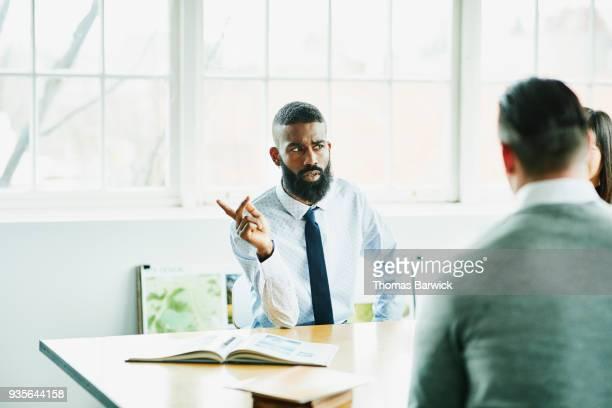 Businessman asking a question during client meeting in office conference room
