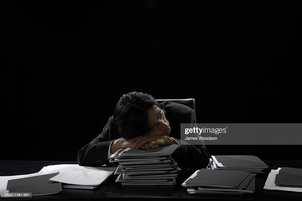 Businessman asleep at desk resting head on stack of files : Stock Photo