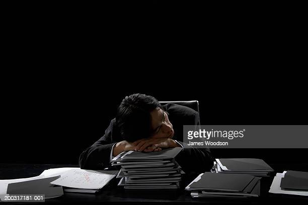 businessman asleep at desk resting head on stack of files - 働き過ぎ ストックフォトと画像