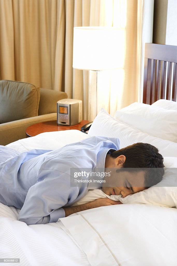 Hotel Room Photography: Businessman Asleep On Bed In Hotel Room Stock Photo