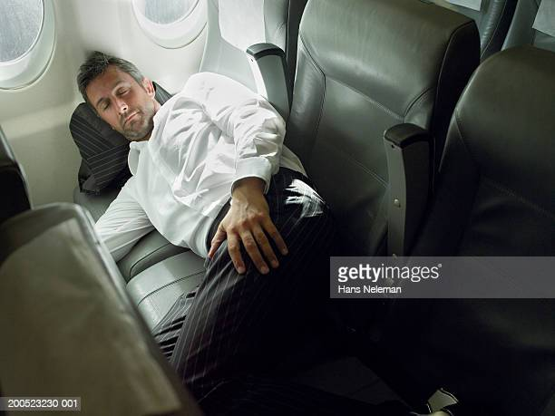 Businessman asleep on passenger seats in aero plane