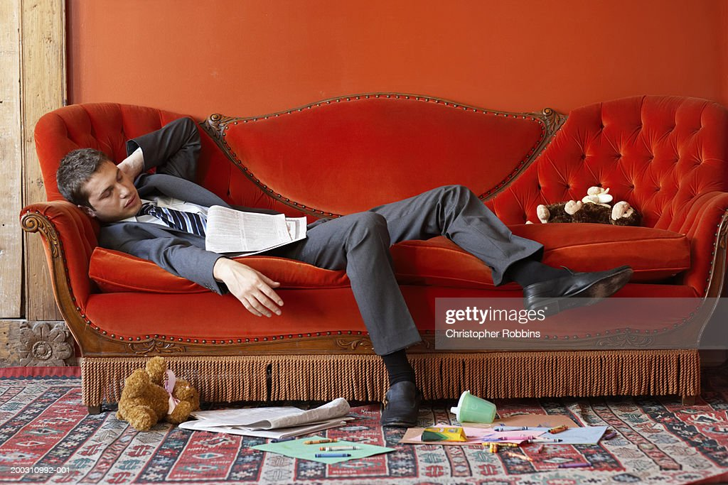 Businessman asleep on sofa surrounded by toys : Stock Photo