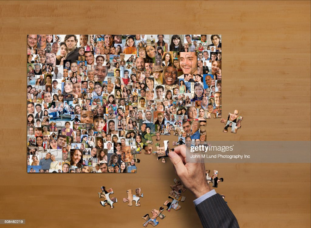 Businessman assembling puzzle of collage of smiling face : Stock Photo