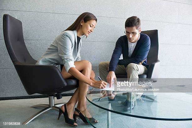 Businessman assisting businesswoman in signing document