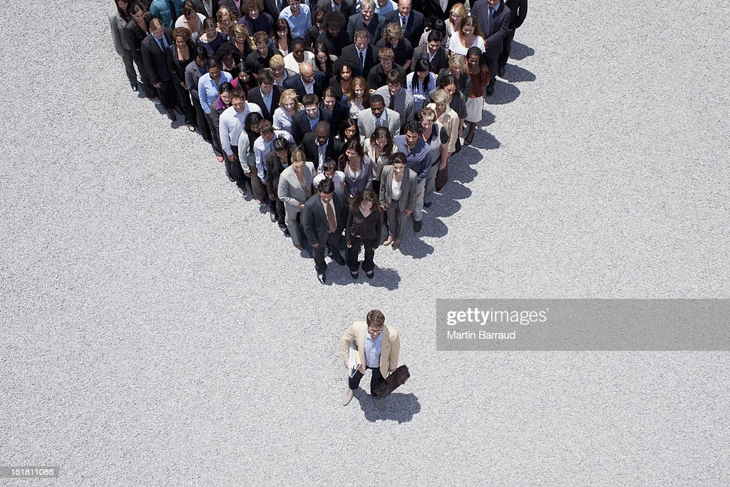 Businessman at apex of pyramid formed by crowd : Stock Photo