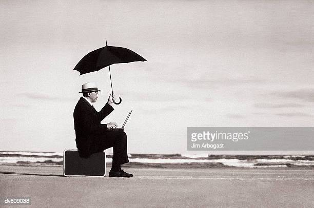 Businessman at Beach with Umbrella and Laptop