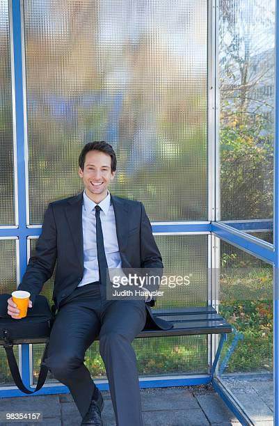 businessman at bus stop, waiting, happy