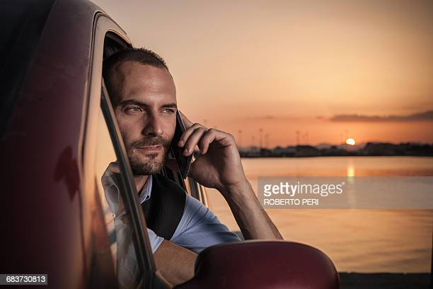 businessman at car window talking on smartphone at sunset on coast, cagliari, sardinia, italy - muscle men at beach stock photos and pictures