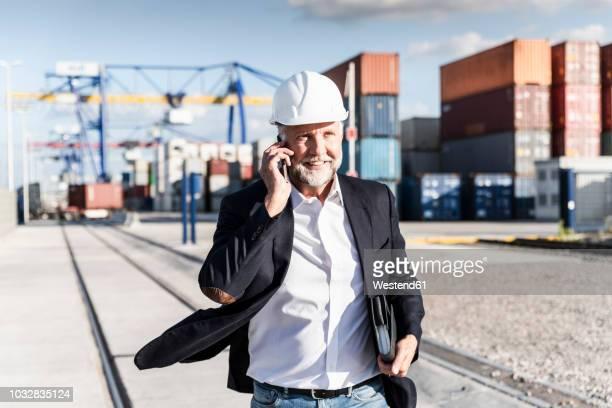 businessman at cargo harbour, wearing safety helmet, using smartphone - logistik stock-fotos und bilder