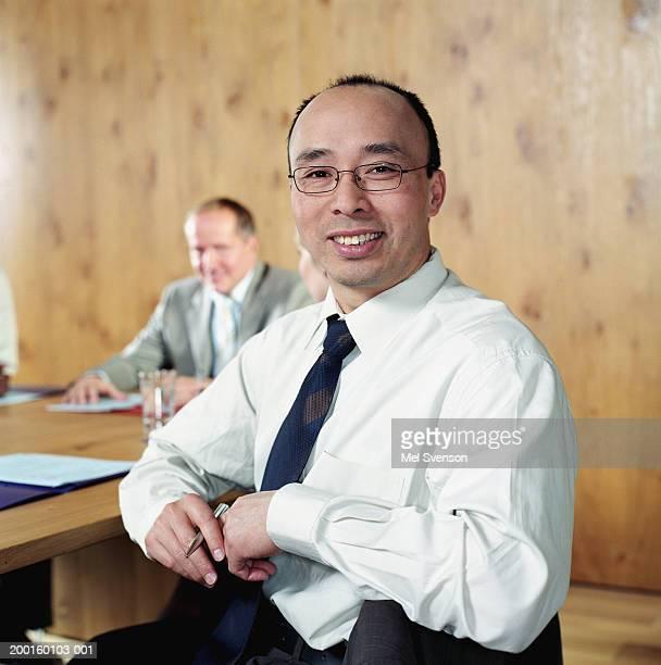 Businessman at conference table, smiling, portrait