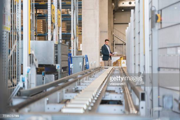 Businessman at conveyor belt in factory