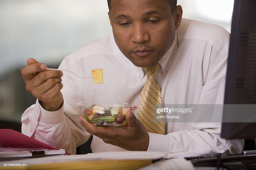 Businessman at desk eating fruit salad and reading document : Foto stock