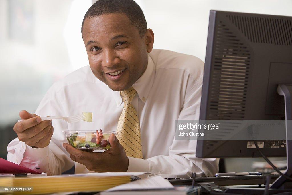Businessman at desk eating fruit salad, smiling, portrait : Foto stock