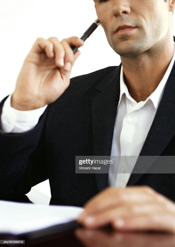 Businessman at desk, holding pencil, close-up : Stockfoto
