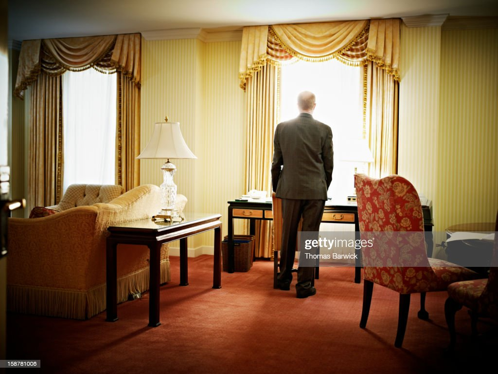 Businessman at desk in hotel looking out window : Stock Photo