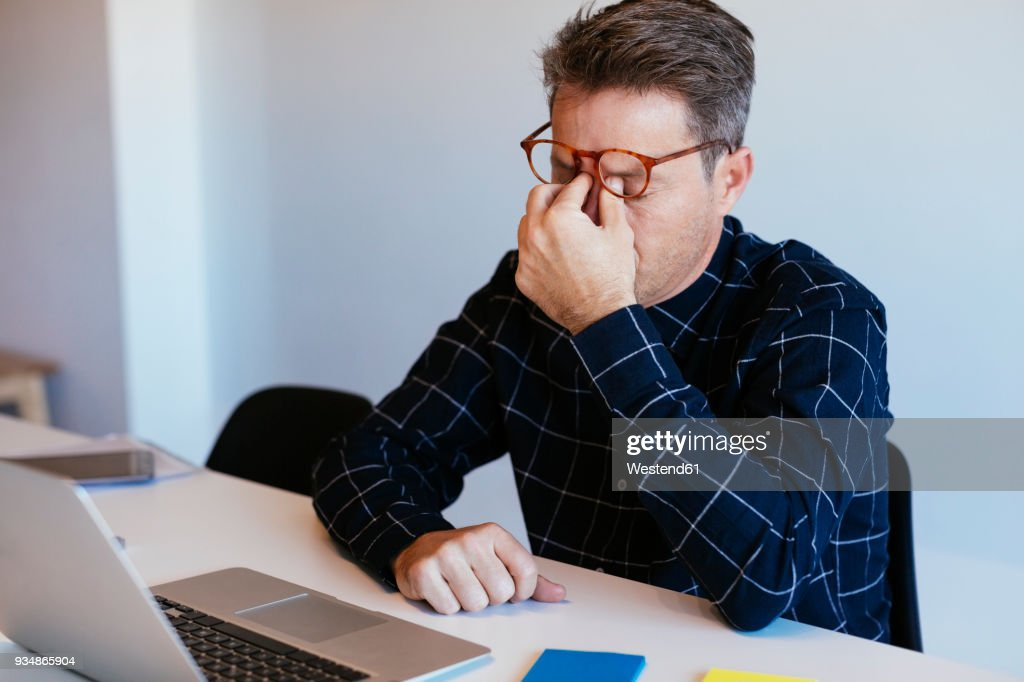 Businessman at desk in office rubbing his eyes : ストックフォト
