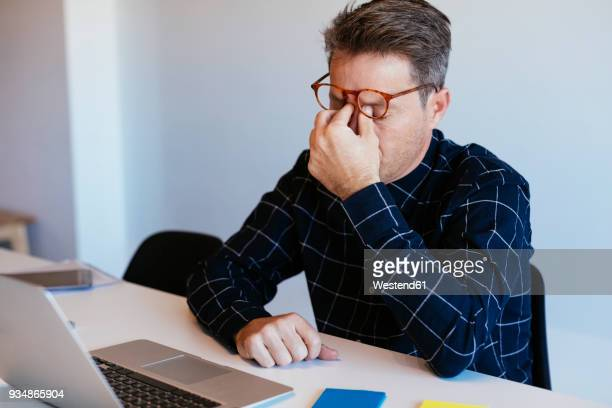 businessman at desk in office rubbing his eyes - stress stock-fotos und bilder