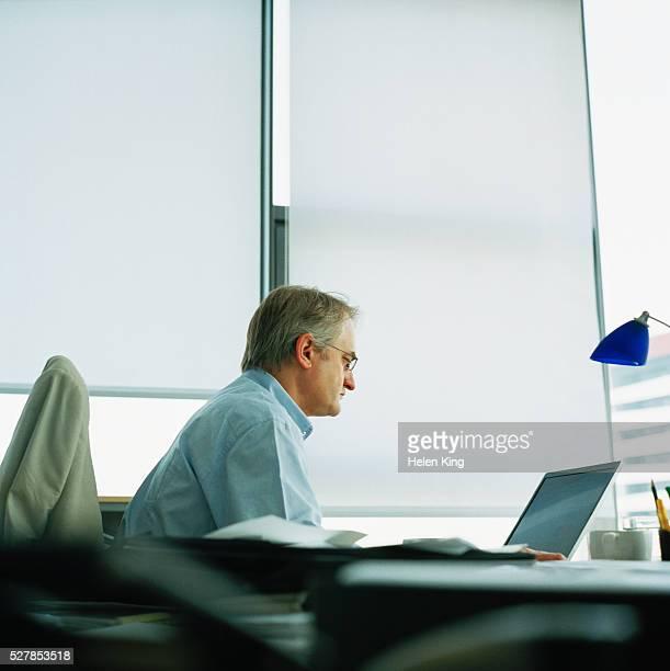 businessman at desk - un solo hombre fotografías e imágenes de stock